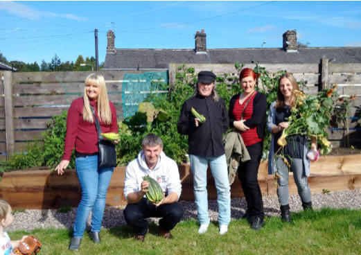 community growing group in Bolton with harvested vegetables they have grown