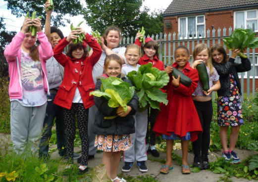 growing group with children and adults hold up produce they have grown