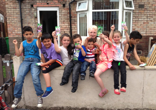 group of children sat holding up seed packets as part of commuity growing project